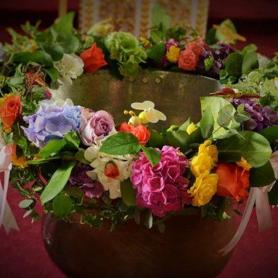 Decor cristelnita cu flori vesele, multicolore : hortensii, eustome, trandafiri, albinute, fluturasi, iedera, in ton cu lumanarea.