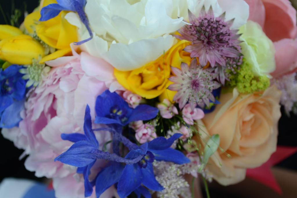 Buchet cununie civila cu delfinium albastru, trandafiri peach, bujori albi, roz si corai, frezii galbene, astrantia roma, alchemilla, panicum si astilbe.